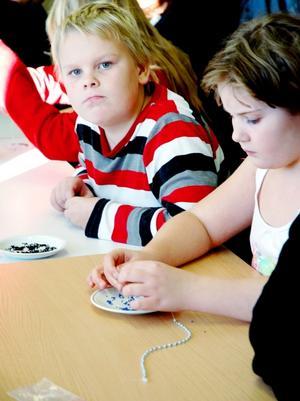 Pärlband. Joel Eklund, 9 år och Maria Lindberg, 11 år är klasskamrater. På måndagen trängdes de bland en massa andra ungdomar och unga vuxna i studiefrämjandets lokaler i Tierp, där det var smyckesverkstad.