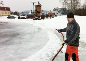 Pelle Andersson från kommunens tekniska kontor räknar med att isbanan i Stadsparken ska kunna tas i bruk av en skrinnande allmänhet under fredagen.