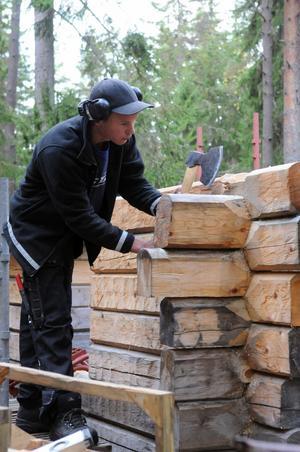 Fredrik Nordin jobbar med yxa vid timring, precis som hantverkare har gjort i tusen år vid husbyggen.