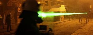Under upploppen i Aten nyligen användes grön laser mot polisen; här är en kravallpolise målet för en dold gärningsman.