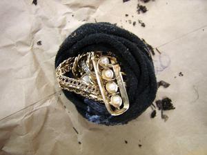 Ur hålet vid en sten drog mannen fram en svart tygpåse som liknade en strumpa och i den låg ytterligare guldföremål. Foto: Polisen