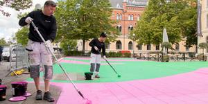 Bjarne Hilmarth och Catrin Gyllander från Kraffts måleri målar upp en variant av Open Arts logotype på Teaterplan. Blåsten har gjort att de får rolla på färgen på plattorna.