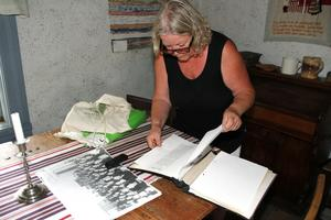 Britt Marie Blidmo Hedlund bläddrar i gamla urklipp som rör Enåker. Bilden på bordet är från en revy som hölls många år på 1950-talet.