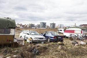 Bortanför husvagnslägret tonar de nybyggda bostäderna på Gävle strand upp sig.