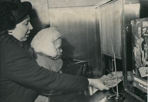 I januari 1948 fick svenska familjer ta emot det allra första barnbidraget. På bilden hämtar fru Anna-Marie Dahl och sonen Claes-Göran ut bidragets 130 kronor på det lokala postkontoret i Stockholm. Foto: TT