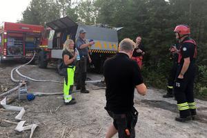 Brandmän och bybor, som hjälper till vid branden, i samspråk.