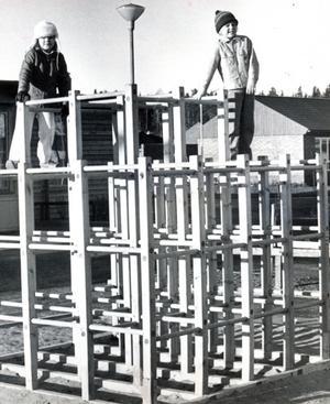 Bjurhovda 8 december 1971. Bildtexten i vlt: En bra skolgård, tycker Anna-Lena Krantz och Richard Kouppala och klättrade upp i klätterställningen på Östra Bjurhovdaskolans gård. Sandlåda, klängställning, bänkar, bord  och pingisbord finns också på den här skolgården.