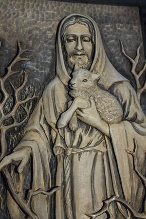 Många av Lina Erikssons motiv var religiösa. Även detta snidade konstverk är gjort i ett enda trästycke, föreställande Jesus med ett lamm i famnen.