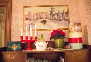 Julfint i köket med en klassisk bonad och söta kakburkar.