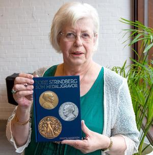 """""""Jag är jätteglad för det här, och trodde aldrig att det skulle bli en bok"""" säger Birgitta Sandström som kallar sig själv nörd när det gäller medaljer av Tore Strindberg."""