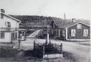 På bilden från 1905 ses Wedins handelsbod till vänster, till höger Bomstugan där resenärer var tvungna att betala tull för att få passera bron över Ljungan. I förgrunden Karl XIV Johans minnessten som restes av Njurunda församling till minne av hans besök i Västernorrland den 21 augusti 1835 då han firade sin 25-årsdag som Sveriges regent.