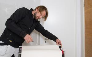 – Vi tar till hela dygnet och alla knep som finns i boken för att bli klara med renoveringen i tid, säger Johnnie Krigström. Här mäter och limmar han tapet som ska upp i hallen.
