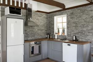 Köket går i grått med tegelväggar. Foto: Notar