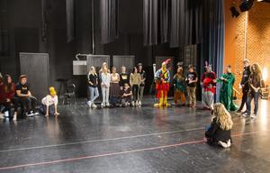 Under föreställningen sitter publiken på scenen. Gröna och röda tejpmarkeringar visar vilket område skådespelarna ska hålla sig inom.