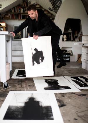 Jesper Waldersten brer ut några av bilderna som han har gjort till