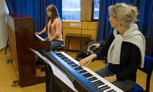 """Jennifer Lundh, pianospelare och Malena Stadigs, pianolärare under uppvärmningen. """"Det är bra att den här inriktningen finns på gymnasiet i Köping. Vissa har gått på musikprofil på Kabbe innan och så när de kommit hit var det inget mer med musiken, men nu finns den möjligheten"""", säger Malena."""