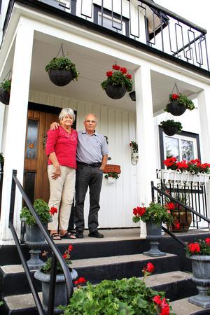 Louise-Marie och Claes Kjellin på gården i Badelunda. De röda pelargonerna pryder hela husets utsida.