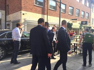 En jäktad statsminister anländer. Säpovakter håller koll och bildar en säkerhetsmur.