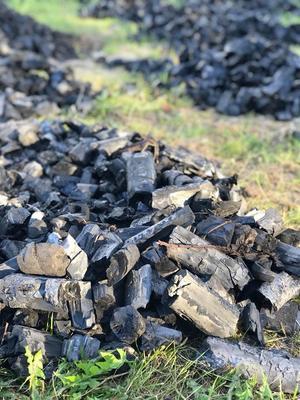 Det vackra svarta och gnistrande björk-kolet ligger och svalnar inför packning.