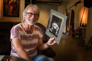 Thomas Ljungqvist med ett av självporträtten i hans samling.