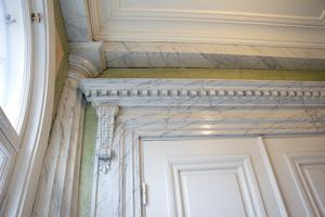 Dörrarnas överstycken är rikt ornamenterade.