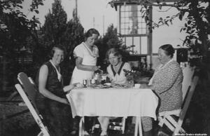 1940-tal. Fika i trädgården på Pilgatan 9 (nu 13), Hagaby. Från vänster: okänd, Frideborg 'Bojan' Malm, okänd, Augusta Malm. Bildkälla: Örebro stadsarkiv/fotograf okänd.