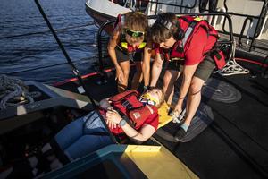 Monica Wounder och Charlie Magnusson bär ner en skadad i sjöräddningens båt.