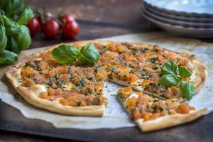 Pizza med färska tomater och gröna blad.