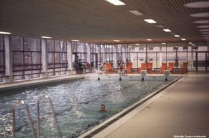 Eyrabadet 1977. I dag finns bubbelpoolen på den plats där de orange stolarna fanns då. Foto: Örebro stadsarkiv/okänd fotograf