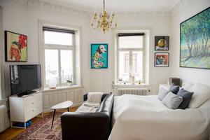 Ovanför sängen hänger en jättemålning av Lars-Åke Högstedt. De höga fönstren släpper in mycket ljus i sovrummet.