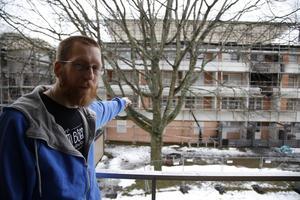 Från sin nya balkong kan Andreas se över till sin gamla lägenhet i det eldhärjade huset.