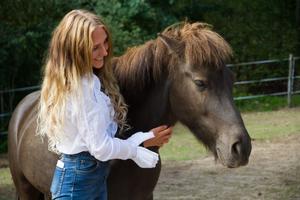 Moa Enqvist Stefansdotter med sin egen häst på gården hemma i Embjörs.