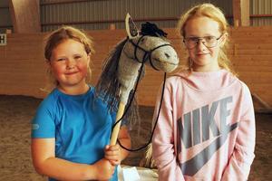 Alma och Maja Göthe med en hemmagjord käpphäst. Det är Kerstin Yman som tillverkat den av en gammal socka.
