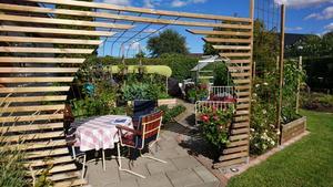 På väg in i köksträdgården. Roland har skapat den runda portalen. Tarja kom med idén efter en bild hon sett på Pintrest. Foto: Privat