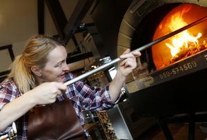 Lena Flaten tycker om att använda eld i sin matlagning, som här i restaurangen vedeldade ugn.