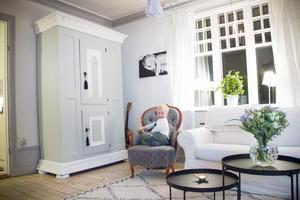 I vardagsrummet står det gråmålade allmogeskåpet som de tidigare ägarna lämnade kvar. Fyraåriga Philip har krupit upp i fåtöljen och på väggen ovanför hänger ett babyfoto av honom.