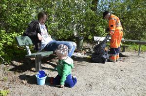 Nära lekplatsen. Mats Lindholm och hans Teodor försöker koppla av. Maj-Britt plockar skräp.