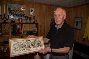 I källaren i villan i Söderhamn finns minnena samlade. Här är en tavla som med karikatyrteckningar porträtterar de svenska mästarna 1964.