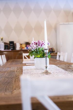 I matsalen står ett stort träbord med vita stolar. I dag äter hotellets gäster sin frukost här.