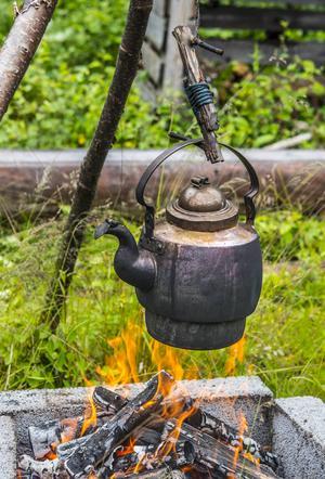 Ovanför elden hänger kaffepannan.