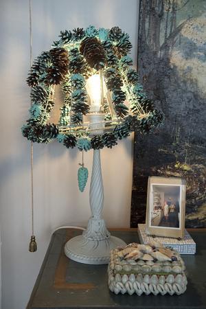 Lotta Kühlhorn gjorda lampan själv genom att plocka kottar, trä upp dem på trådar, måla dem med vanlig väggfärg och sedan fästa dem på en gammal lampskärm.