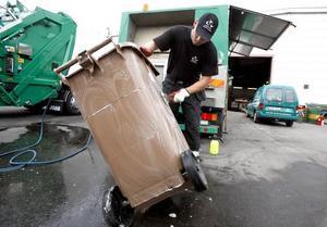 Mattias har sprutat såpa på utsidan av ett kompostkärl och skrubbar nu bort värsta smutsen med en borste.