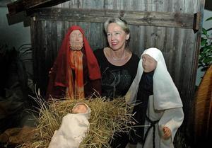FAMILJEN. Monica Uppman har skulpterat alla ansikten i julkrubban. Här sitter hon intill Jesusbarnet med Josef och Maria.