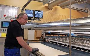Bo Sundström arbetar med att fästa det tunna lagret av träfanér på panelskivorna.