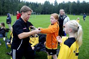 Hjälper till. Lagledaren Camilla Asplund hjälper Wilma Sjöberg med målvaktshandskarna inför andra halvlek i matchen mot Hällefors F10:or. Wilma Soreby tittar på.