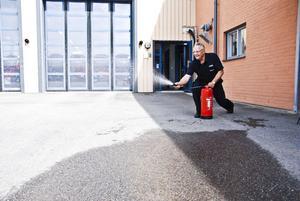 Instruktören Ove Wiström visar hur en övning kan gå till med brandsläckare.