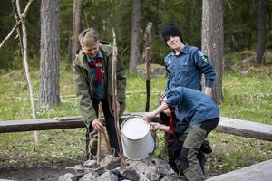 Vid städningen i stugan häller Simon Eklind och Jakob Pettersson ut askan i lägerelden.