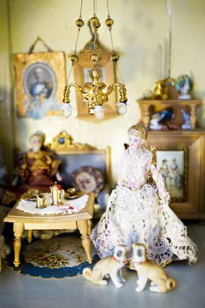 Takkronan är en Ormolu från 1800-talet med en dramatisk historia. Docka med huvud av biskviporslin med klänning av siden och spets.