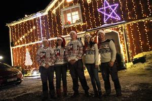 Mikael, Malin, Joakim och Emma Sjöberg tillsammans med Emmas pojkvän Conny Berglund poserar framför familjens stolthet – det julpyntade huset i Hamrångebygden.
