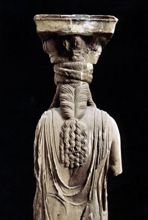 En marmorkaryatid med sin fantastiska frisyr, från cirka 415 före Kristus. Hon står nu i det nya Akropolismuseet, och i Erekteion är hon ersatt av en kopia.